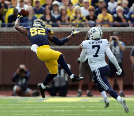 Amara Darboh (82) of the Michigan Wolverines pulls in a pass with Micah Hannemann (7) of Brigham Young  defending during NCAA football in Ann Arbor, Michigan, Saturday, Sept. 26, 2015.