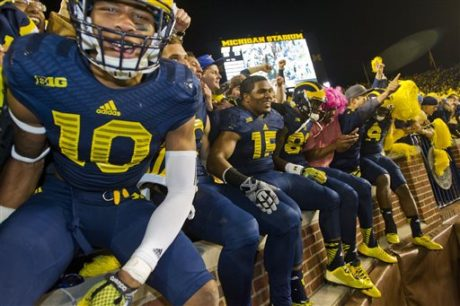 Michigan wide receiver Da'Mario Jones (10) and teammates celebrate with fans in the student section of Michigan Stadium after an NCAA college football game against Penn State in Ann Arbor, Mich., Saturday, Oct. 11, 2014. Michigan won 18-13. (AP Photo/Tony Ding)