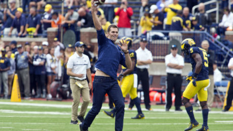 Former Michigan and currently suspended New England Patriots quarterback Tom Brady throws the football on the field before an NCAA college football game against Colorado at Michigan Stadium in Ann Arbor, Mich., Saturday, Sept. 17, 2016. (AP Photo/Tony Ding)